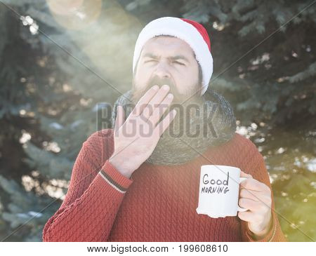 yawning handsome man in santa claus hat bearded hipster with beard and moustache suffers from hot drink in cup with good morning text on sunny winter day outdoors on natural background
