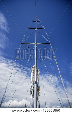Mast in cloudy sunny day with sails summer time.
