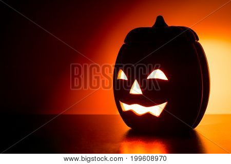 Halloween pumpkin head Jack o' Lantern illuminated on wood table.