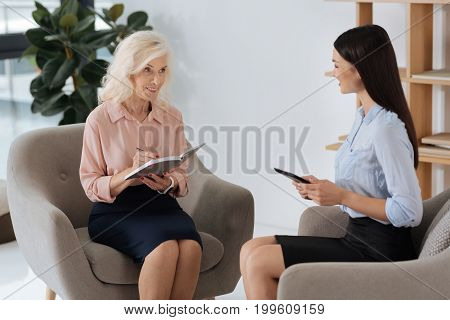Work in team. Pleasant delighted elderly woman holding a notebook and taking notes while sitting opposite her colleague