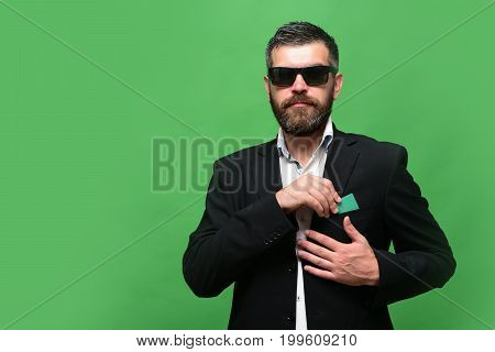 Guy with satisfied face and sunglasses isolated on green background. Man with beard puts green business card into pocket. Business and people at work concept. Businessman with empty card copy space