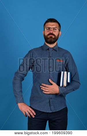 Textbooks In Blue Color In Guys Hand On Blue Background