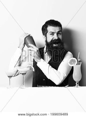handsome bearded barman with long beard and mustache has stylish hair on smiling face holding shaker and made alcoholic cocktail in vintage suede leather waistcoat on purple green studio background