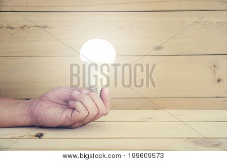 Hand holding LED lamp with lighting bulb on wood background. Innovation and idea concept.