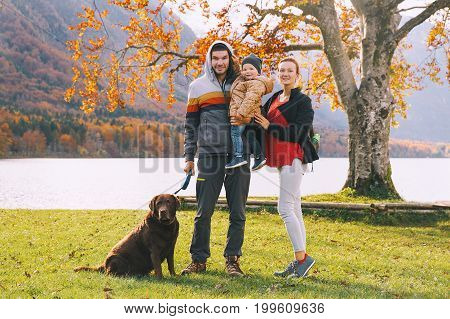Portrait of happy family: Mother father child and dog outdoors. Autumn on Lake Bohinj Slovenia Europe. Beautiful sporty family spends the fall holidays on nature.