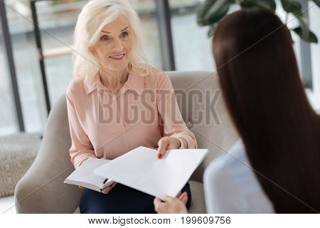 Important papers. Close up of an office document being given to a nice positive elderly woman