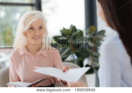 This is for you. Joyful friendly elderly woman looking at her colleague and giving her a document while working together with her