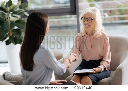 Welcome to our team. Happy joyful nice women sitting opposite each other and shaking hands while having a job interview