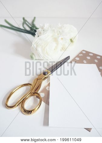 Styled stock photo. Feminine digital product mockup with buttercup and daffodil flowers, blank list of paper and golden scissors. White background. Flat lay, top view, picture for blog, social media.