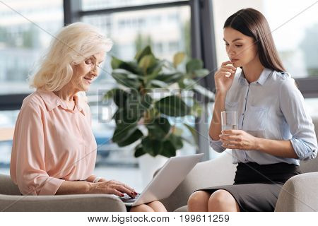 Being thirsty. Beautiful pleasant young woman holding a glass and drinking water while looking at her senior colleague