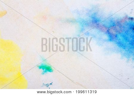 Macro shot of abstract hand drawn blue and yellow watercolor paints background. Stained texture