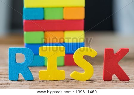 risk concept with colorful wooden alphabets RISK and wooden blocks tower in the background.