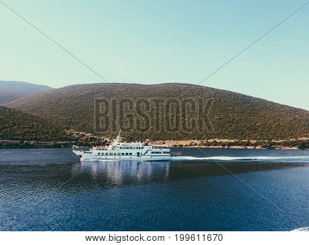 Extraordinary Landscape Of Mountain Penetrating The Blue Sea Water. White Ship With Tourists Floatin