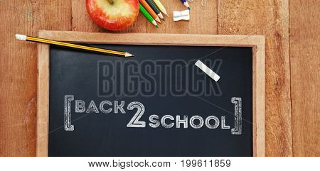 Back to school text over white background against overhead view of chalkboard with pencils and apple