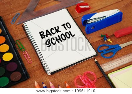 Back to school text on white background against school supplies on wooden table