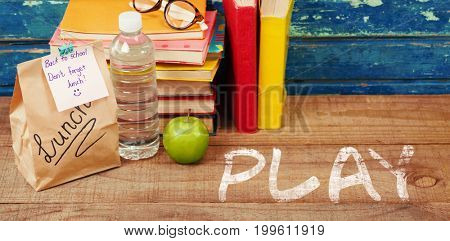 Play text against white background against books with packed lunch on table