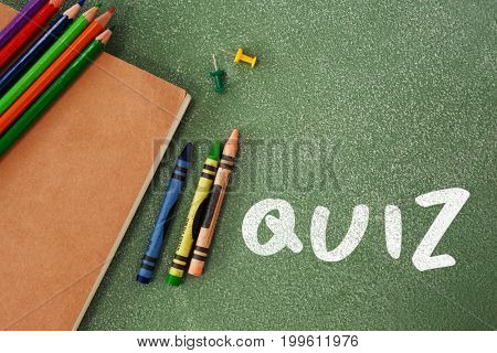 Quiz text against white background against high angle view of crayons and book