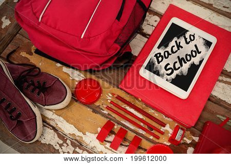 Back to school text on pink splash against high angle view of bag with tablet and shoes on table