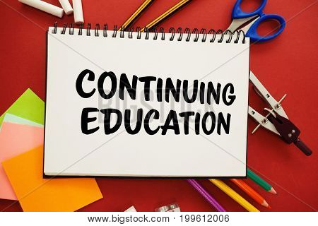 Continuing education text against white background against overhead view of spiral notebook with pencils