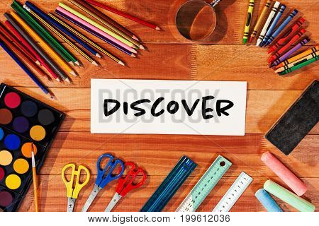 Discover text on white background against directly above shot of blank paper with school supplies
