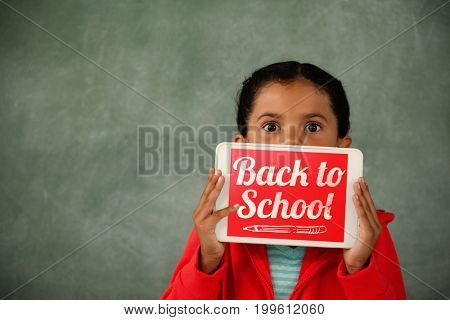 Back to school text over white background against girl holding digital tablet against chalk board in classroom