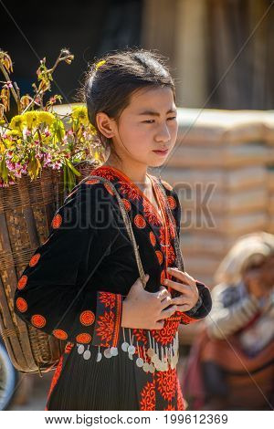 CHIANGMAI THAILAND - JANUARY 25 2015: Hill tribe girl backpack with bamboo basket of flowers in parade of 22nd Traditional Skirt Fabric and The Indigenous Product and Culture Festival in Mae Chaem Chiangmai Thailand