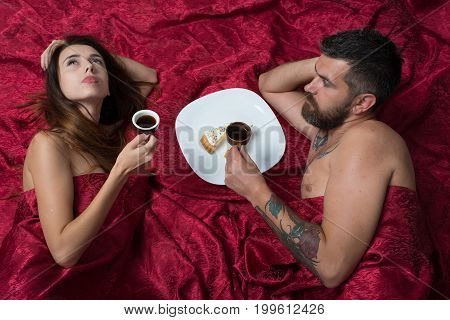 Man with beard having romantic breakfast with pretty lady in bed top view. Love and sex concept. Man and woman with half covered bodies. Couple in love lies on burgundy sheets.