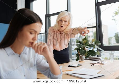 Go away. Angry unhappy senior woman looking at her employee and shouting at her while pointing at the door