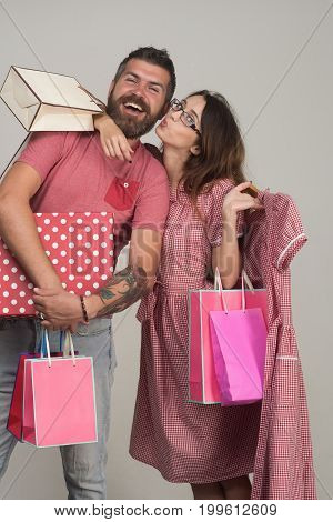 Bearded Man Dressed In Pink Smiles. Couple Holding Shopping Bags