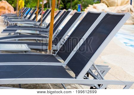 rows of empty modern style beach pool recliner chairs good background for low season or slow business