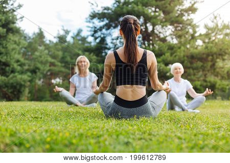 Time for meditation. Delighted females feeling happiness and keeping eyes closed while sitting on the grass in yoga pose
