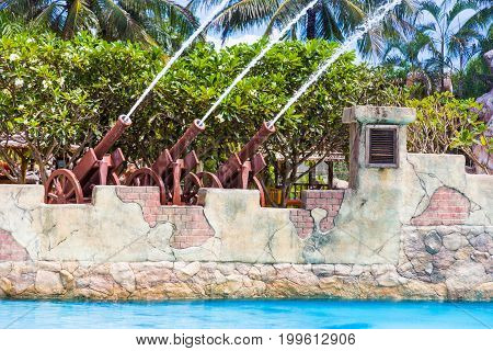 rows of water cannons shooting out water into the pool at a water park in Phuket Thailand