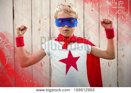 Portrait of superhero boy with arms raised against wooden background