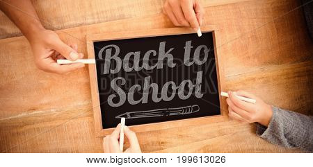 Back to school text over white background against hands writing on chalkboard