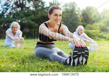 Self-confident. Attractive young instructor keeping smile on her face and putting hands on sneakers while looking forward