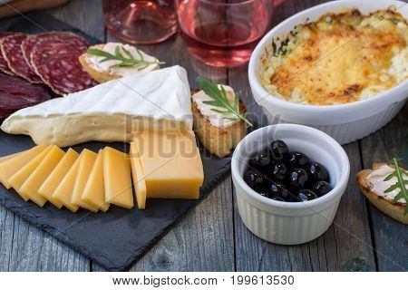 Board with basturma, salami, camembert, cheese, other delicacies and pink wine.