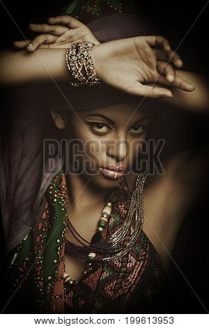 African black young woman beauty portrait with turban headscarf and traditional  clothes studio shot