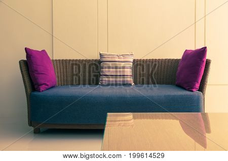 empty modern design wicker sofa with 3 pillows and empty wall room for text or copyspace good background for minimal lifestyle theme