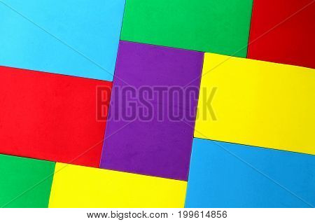 Multicolored background of sheets of cardboard on the table