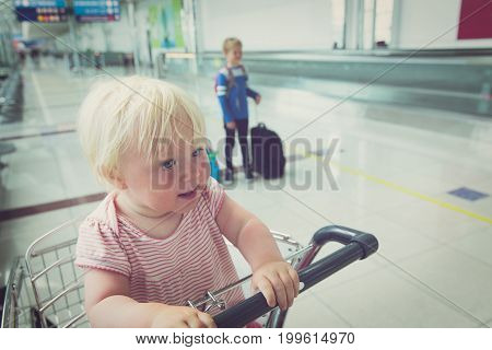 family with kids travel in airport- baby in cart and little boy with suitcase