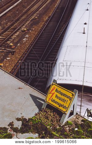 Yellow sign warning for high voltage contact wires above the rails, and white speed train in the background.