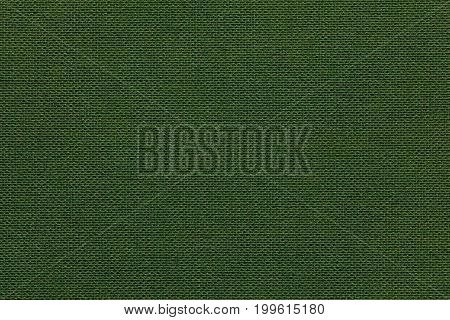 Dark green background from a textile material with wicker pattern closeup. Structure of the olive fabric with natural texture. Cloth backdrop.