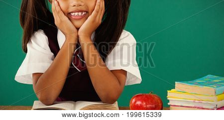 Portrait of schoolgirl reading a book against green background