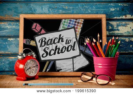Back to school text on paper with pen against blackboard with alarm clock on table