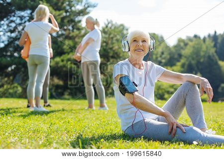 Like my lifestyle. Healthy mature woman expressing positivity and sitting on the grass while listening favorite song