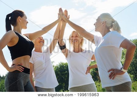 Lets start. Happy pensioners touching hands and looking upwards while keeping smiles on faces