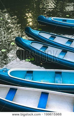 Canoe boats waiting for tourist hire on the lake in municipal city park. Hamburg.