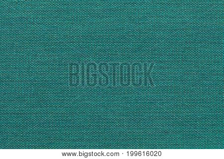 Light turquoise background from a textile material with wicker pattern closeup. Structure of the emerald fabric with natural texture. Cloth backdrop.