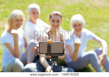 My gadget. Silhouettes of happy women that sitting on the grass and posing on camera while relaxing after training