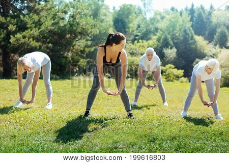 Bend down. Healthy pensioners bowing their backs while doing task and holding legs on shoulder width